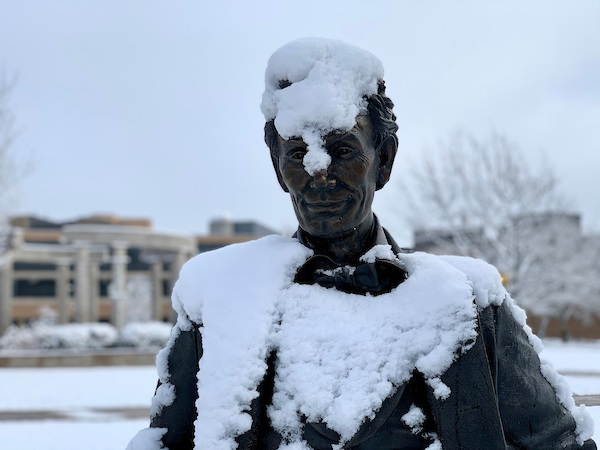 Photo of the UIS Young Lincoln statue covered in snow