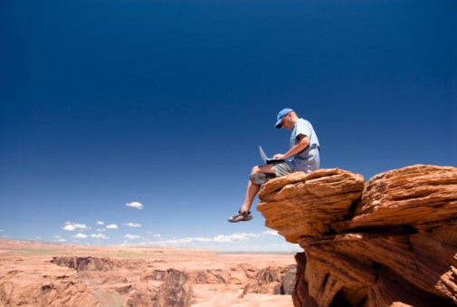 Man sitting on rock outcropping using a laptop computer.