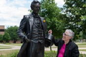 Interim Chancellor Karen Whitney, Ph.D., with the young Abraham Lincoln statue on the UIS quad