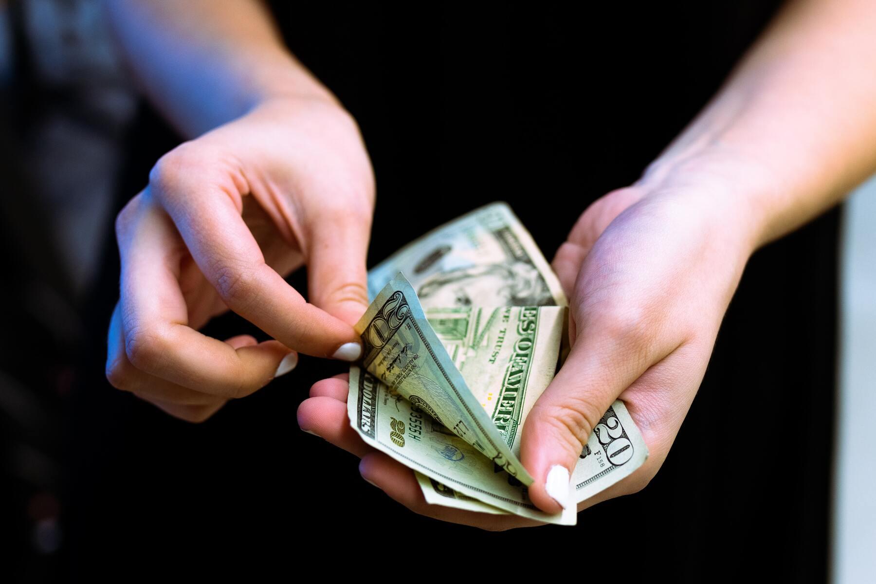 Photo of woman's hands holding dollar bills