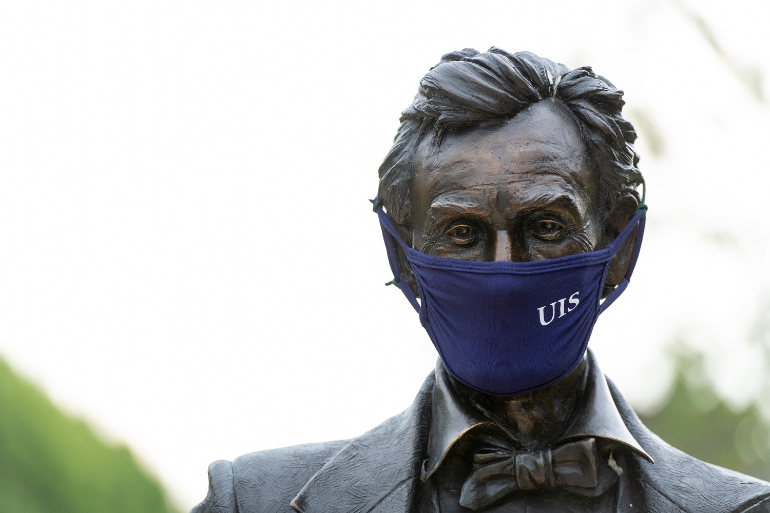 Photo of the UIS Young Lincoln statue wearing a mask
