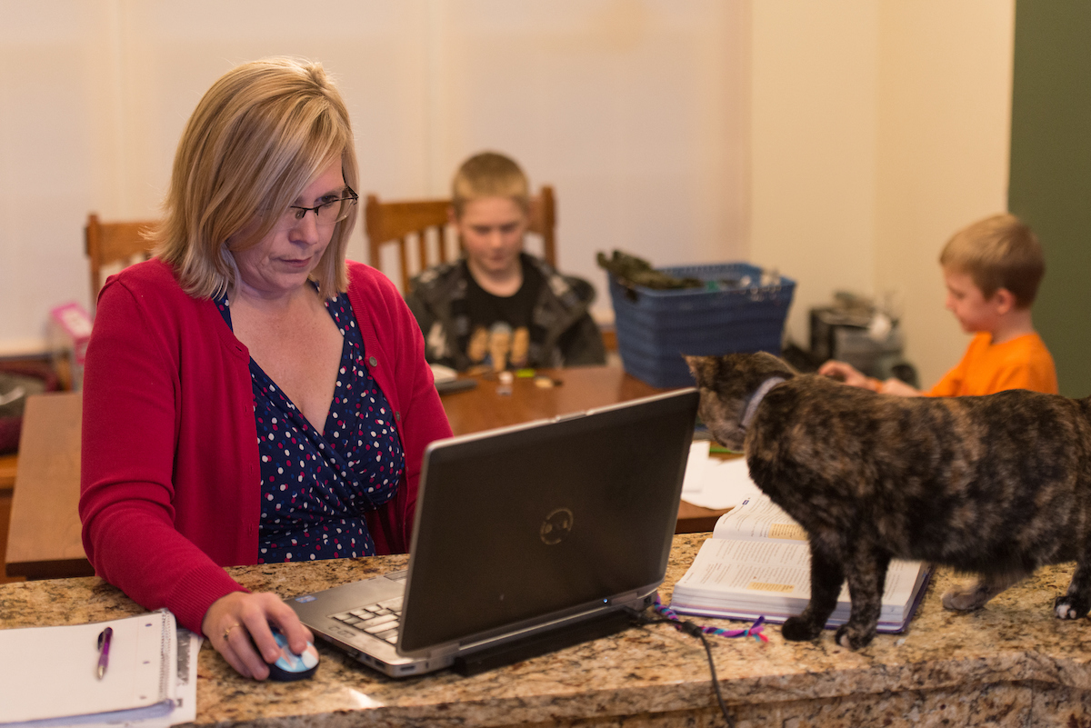 Woman working on laptop at home with family in the background